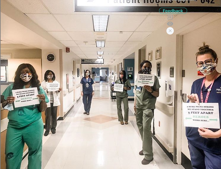 Hospital staff in scrubs and face masks holding signs