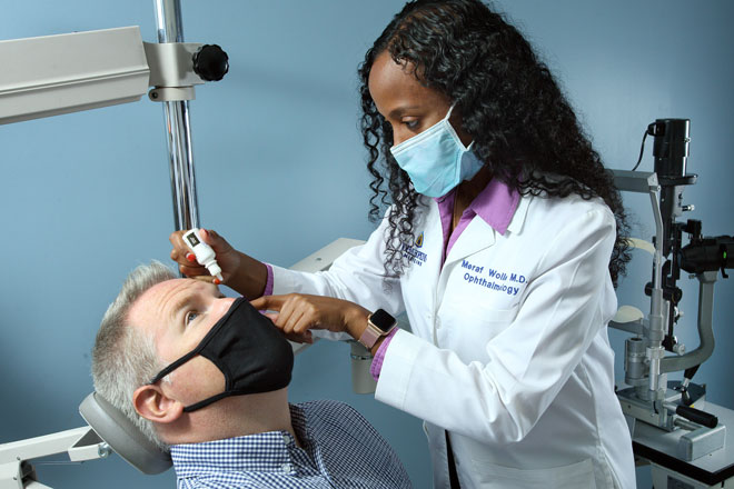 Dr. Meraf Wolle treats the eye of a patient