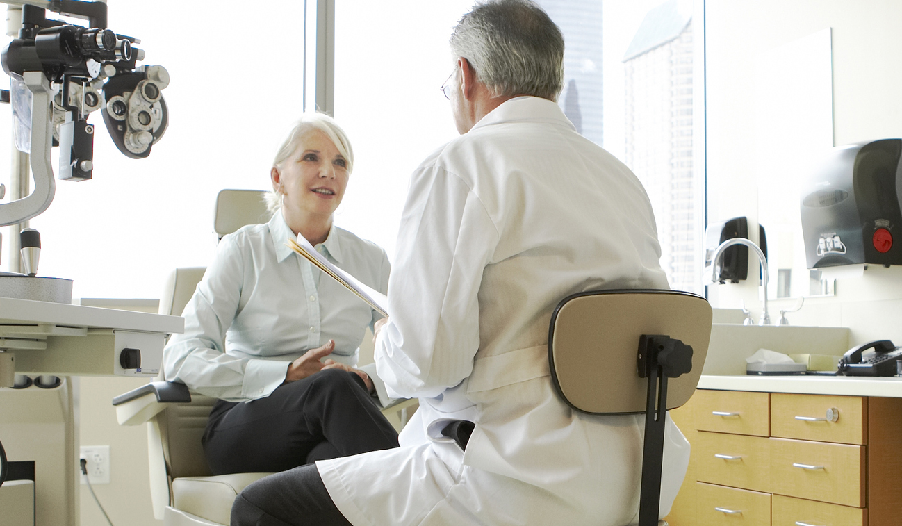 an eye doctor speaks with a patient in the office