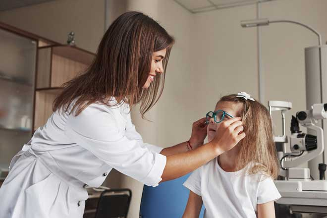 an Optometrist fits a young child for glasses