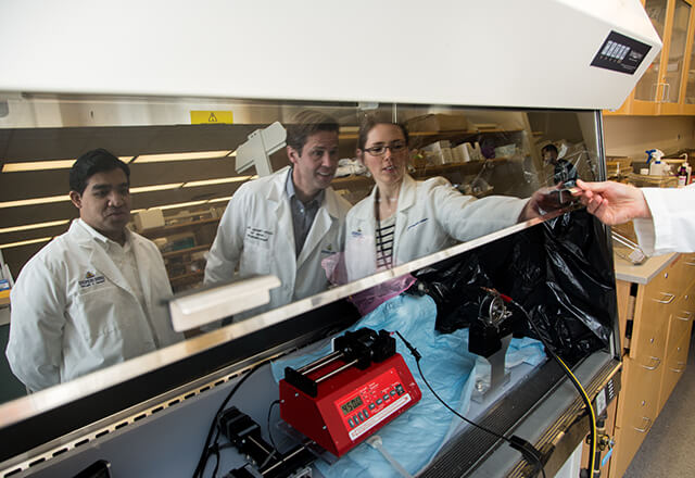 researchers huddle around tool