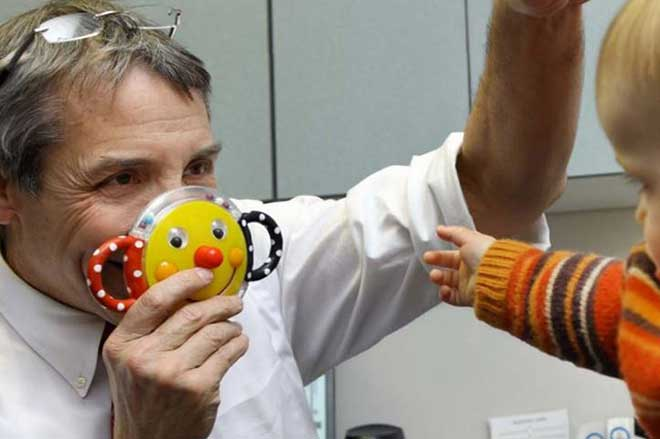 Dr. Michael Repka entertains child patient