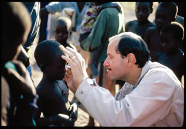 Alfred Sommer observes a patient in Africa