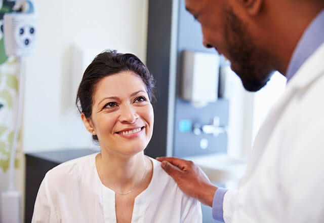 A Patient listens to her doctor while smiling